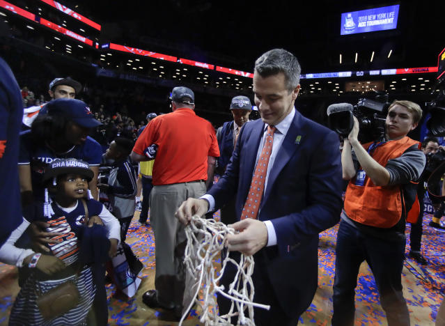 <p> Virginia coach Tony Bennett walks off the floor with one of the nets after Virginia defeated North Carolina 71-63 in an NCAA college basketball game for the Atlantic Coast Conference men's tournament title Saturday, March 10, 2018, in New York. (AP Photo/Julie Jacobson) </p>