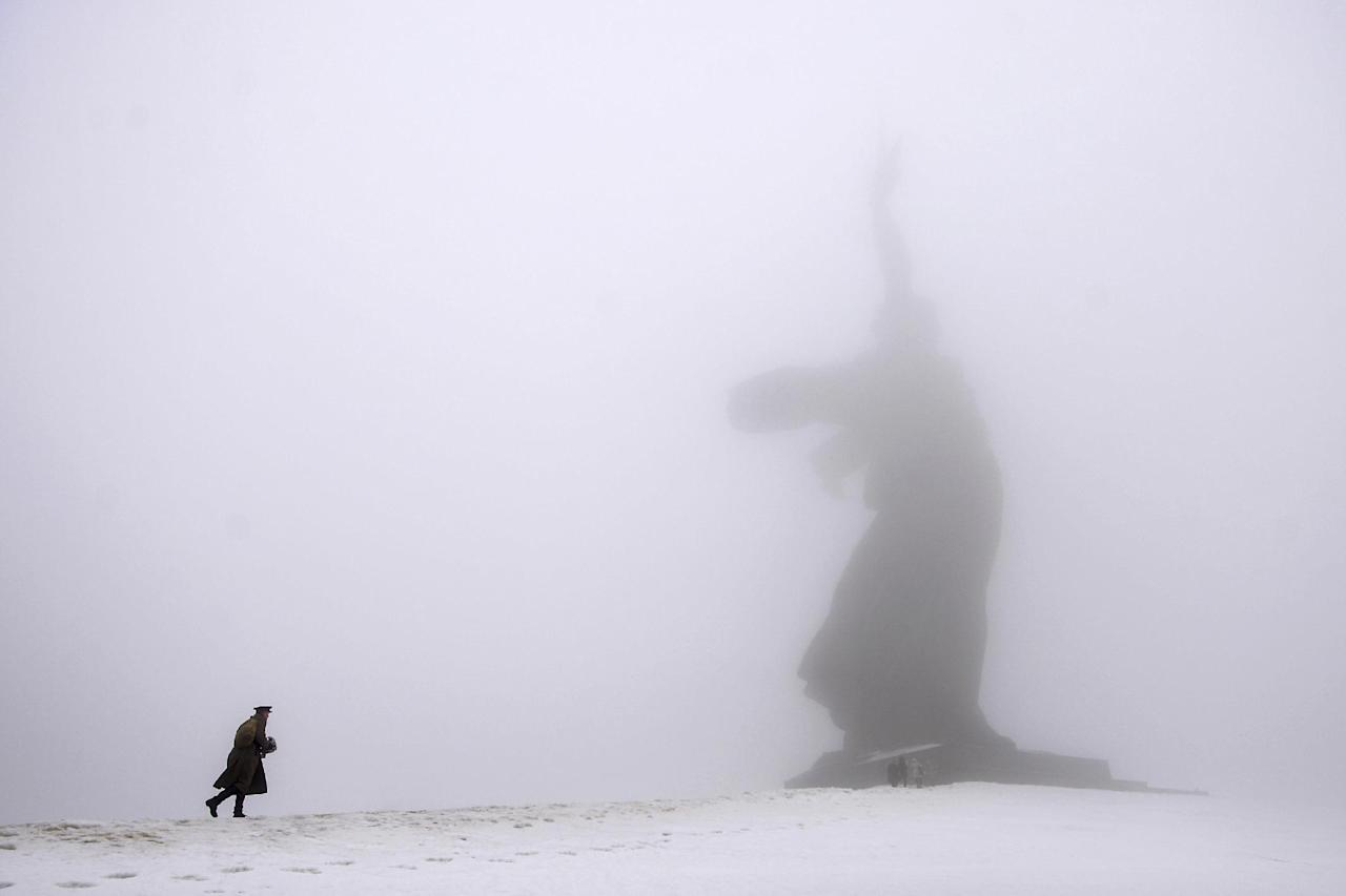 A man dressed in Red Army World War II uniform walks toward the monument to Motherland during ceremonies marking the 72nd anniversary of the Battle of Stalingrad in the southern Russian city of Volgograd, once known as Stalingrad, Monday, Feb. 2, 2015. The city, which was known as Stalingrad during World War II, suffered six months of intensive fighting that ended with the Red Army's defeat of the Nazis, which marked a decisive turn in World War II. (AP Photo/Dmitry Rogulin)