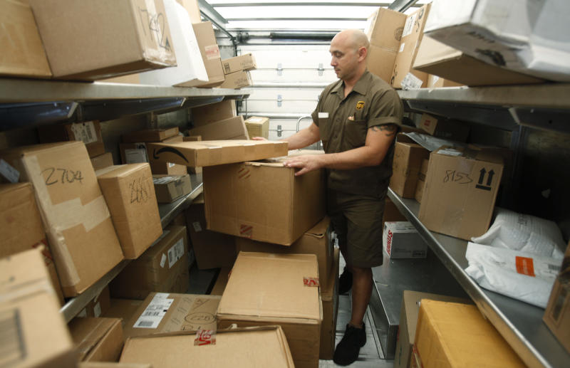 In this Oct. 18, 2010 photo, United Parcel Service (UPS) driver Paul Musial sorts packages in his truck in Palo Alto, Calif. UPS is increasing its earnings forecast for the year after reporting its third-quarter earnings jumped 81 percent Thursday, Oct. 21, 2010. (AP Photo/Paul Sakuma)