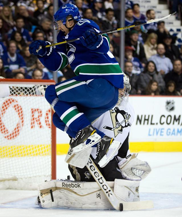 Vancouver Canucks' Henrik Sedin, left, of Sweden, jumps as Pittsburgh Penguins' Marc-Andre Fleury makes the save during the first period of an NHL hockey game Tuesday, Jan. 7, 2014, in Vancouver, British Columbia. (AP Photo/The Canadian Press, Darryl Dyck)