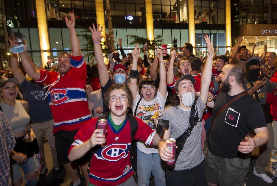 Montreal Canadiens fans celebrate on Rue Rene Levesque after the Montreal Canadiens defeated the Vegas Golden Knights in overtime in Game 6 of an NHL hockey Stanley Cup semifinal playoff series Thursday, June 24, 2021 in Montreal. (Peter McCabe/The Canadian Press via AP)