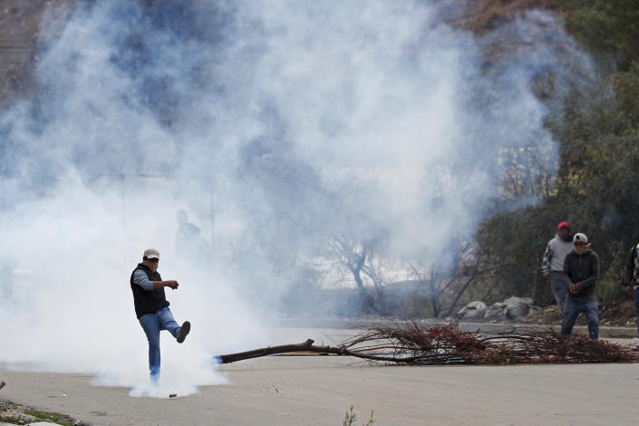 A man kicks a tear gas canister during clashes between police and supporters of former President Evo Morales who set up barricades in La Paz, Bolivia, Monday, Nov. 11, 2019. Morales' Nov. 10 resignation, under mounting pressure from the military and the public after his re-election victory triggered weeks of fraud allegations and deadly demonstrations, leaves a power vacuum and a country torn by protests against and for his government. (AP Photo/Juan Karita)