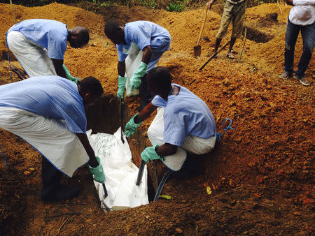 Volunteers lower a corpse, which is prepared with safe burial practices, into a grave in Kailahun