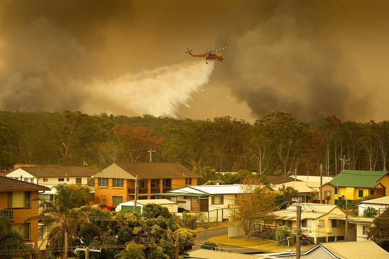 An Aircrane water bombing helicopter drops water on a bushfire in Harrington