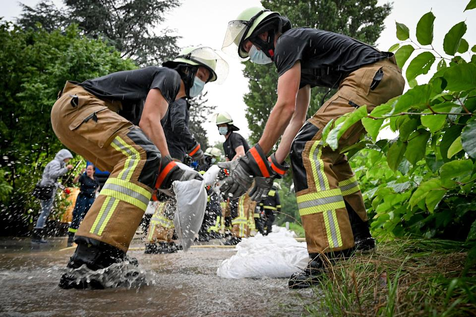 Firefighters and relief workers move sandbags against the rising water level of the River Duessel, in Düsseldorf Grafenberg, Germany on Thursday.