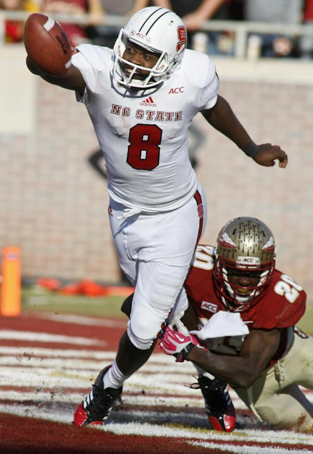 North Carolina State quarterback Brandon Mitchell (8) flips the ball for an incomplete pass to avoid a safety as Florida State defensive back Lamarcus Joyner (20) brings him down in the second quarter of an NCAA college football game on Saturday, Oct. 26, 2013, in Tallahassee, Fla. (AP Photo/Phil Sears)