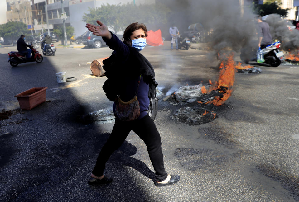 A Lebanese woman shouts slogans against Lebanese politicians, as she passes in front of burning tires to block a main road, during a protest against the increase in prices of consumer goods and the crash of the local currency, in Beirut, Lebanon, Tuesday, March 16, 2021. Scattered protests broke out on Tuesday in different parts of the country after the Lebanese pound hit a new record low against the dollar on the black market. (AP Photo/Hussein Malla)