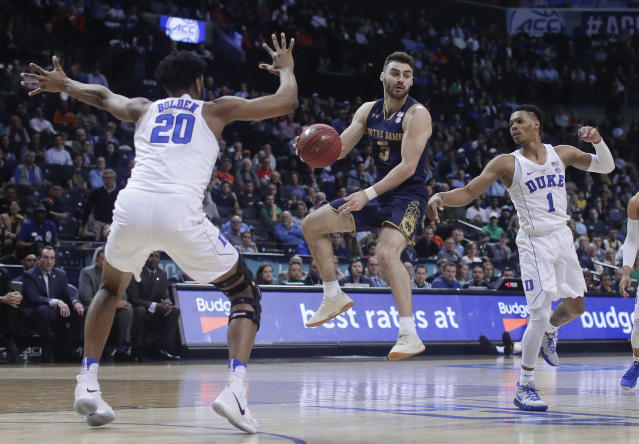 Notre Dame guard Matt Farrell (5) passes off the ball against Duke center Marques Bolden (20) and guard Trevon Duval (1) during the first half of an NCAA college basketball game in the Atlantic Coast Conference men's tournament Thursday, March 8, 2018, in New York. (AP Photo/Julie Jacobson)