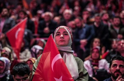 A supporter of the Turkish President stands for the national anthem before his speech in Istanbul, on May 6, 2018