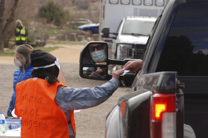 A medical worker hands an updated vaccination card to a motorist at a drive-thru immunization clinic at a motor inn in Mora, N.M., on Tuesday, April 20, 2021. New Mexico is among the states with the highest rates of vaccination for COVID-19. Vaccine crews also traveled down dirt roads to visit homebound elderly residents in sprawling Mora County, with just 4,500 residents who are 80% Latino. First Lady Jill Biden kicked off of a visit to the U.S. Southwest with a tour of a vaccination clinic in Albuquerque. (AP Photo/Morgan Lee)