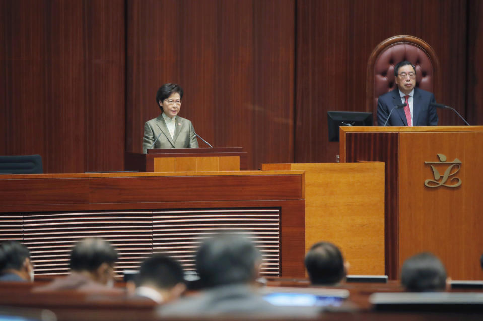 "Hong Kong Chief Executive Carrie Lam, left, delivers her policies at chamber of the Legislative Council in Hong Kong, Wednesday, Nov. 25, 2020. Lam said Wednesday that the city's new national security law has been ""remarkably effective in restoring stability"" after months of political unrest, and that bringing normalcy back to the political system is an urgent priority. (AP Photo/Kin Cheung)"