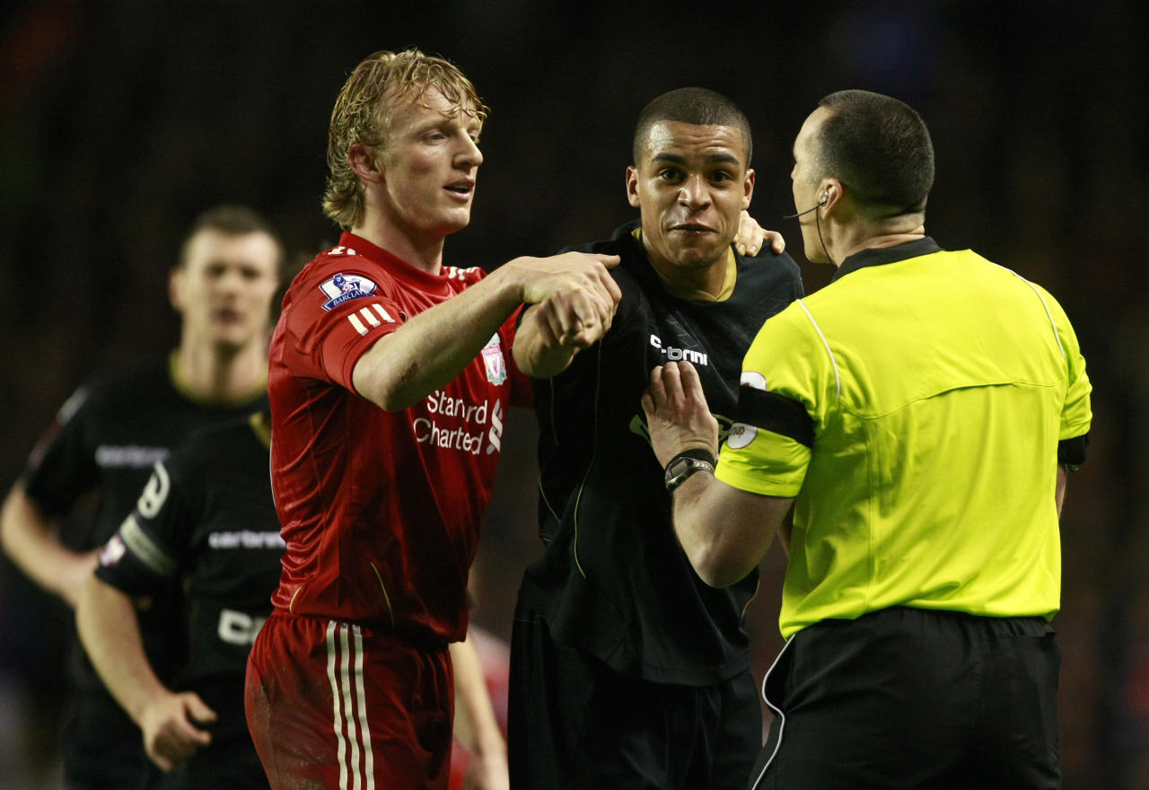 Oldham Athletic's Tom Adeyemi, second right, is calmed by Liverpool's Dirk Kuyt and referee Neil Swarbrick, right, during their FA Cup third round soccer match at Anfield, Liverpool, England, Friday Jan. 6, 2012. The police are investigating an incident in which a black Oldham player appeared to be the target of abuse from Liverpool fans during an FA Cup third-round match on Friday. Oldham right back Tom Adeyemi was visibly upset late in the game at Anfield after seemingly taking offence from something shouted from the Liverpool-supporting area known as The Kop. (AP Photo/Tim Hales)