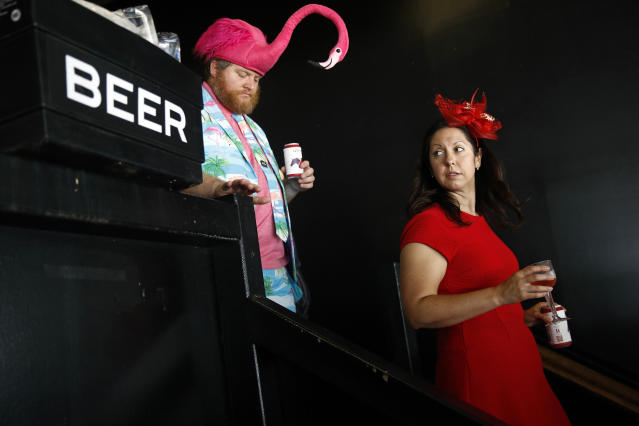 Spectators walk past a case of beer at Pimlico Race Course, Saturday, May 18, 2019, ahead of the Preakness Stakes horse race in Baltimore. (AP Photo/Patrick Semansky)