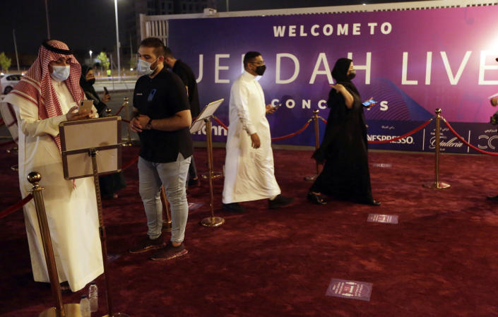 Saudi audience show their coronavirus vaccine online certificate as they enter the concert of prominent Saudi singer Mohammed Abdu at the newly built Super Dome, in Jiddah, Saudi Arabia, late Thursday, July 8, 2021. In the two decades since Sept. 11, 2001, Saudi Arabia has confronted al-Qaida on its own soil, revamped its textbooks, worked to curb terror financing and partnered with the United States to counter terrorism. (AP Photo/Amr Nabil)