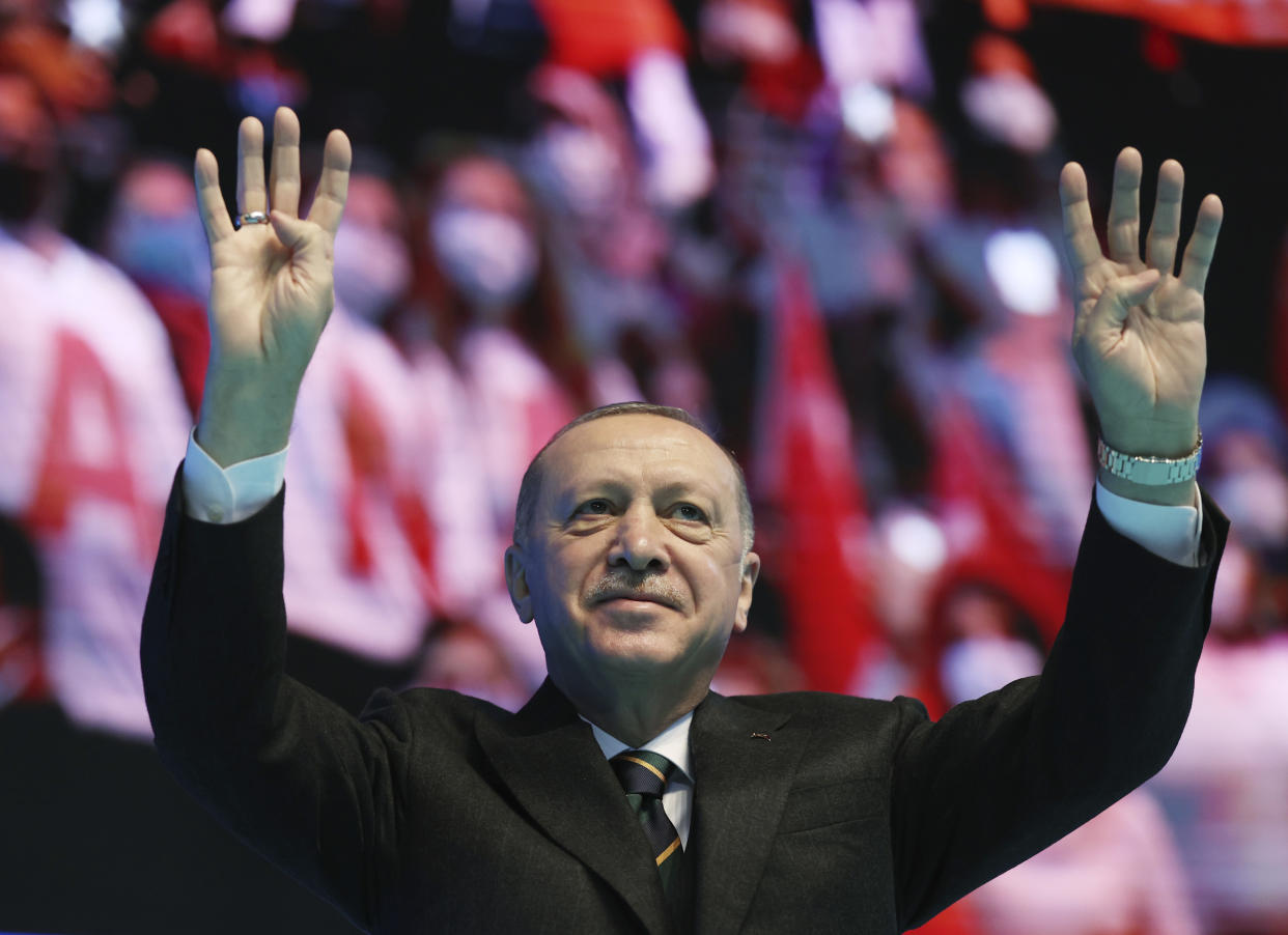 Turkey's President Recep Tayyip Erdogan waves to supporters during his ruling party's congress inside a packed sports hall in Ankara, Turkey, Wednesday, March 24, 2021. Erdogan has come in the firing line for holding the rally inside the closed venue amid a new surge in COVID-19 cases. Thousands of party supporters filled the stands of the 10,400-capacity sports hall in the capital, in disregard of the government's own social distancing rules to fight the coronavirus pandemic. Social media meanwhile, was rife with videos purporting to show busloads of ruling party supporters travelling to Ankara to attend the congress, many of them mask-less. The wearing of masks in public spaces is mandatory. (Turkish Presidency via AP, Pool)