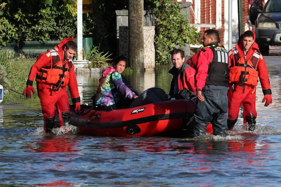 First responders pull local residents in a boat as they perform rescues of people trapped by floodwaters after the remnants of Tropical Storm Ida brought drenching rain,  flash floods and tornadoes to parts of the northeast in Mamaroneck, New York (REUTERS)