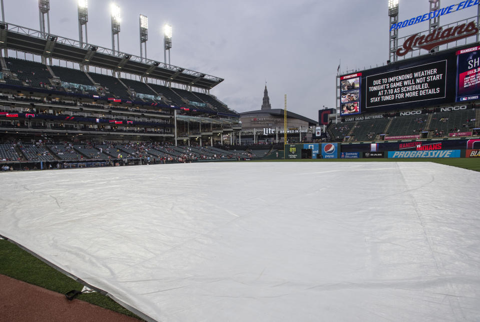 A rain delay before a Cleveland Indians baseball game against the Texas Rangers keeps the field covered in Cleveland, Tuesday, Aug. 6, 2019. The game was eventually postponed. (AP Photo/Phil Long)