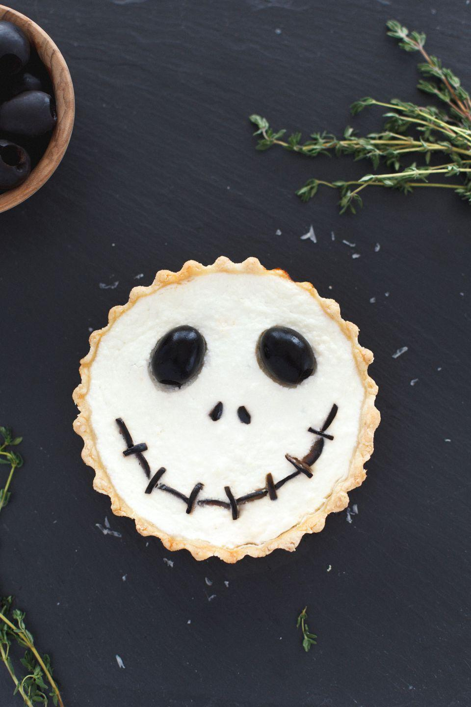 """<p>For a more elevated Halloween dinner menu, consider these refined ricotta tarts that get a dash of whimsy from some cleverly placed black olives. </p><p><a class=""""link rapid-noclick-resp"""" href=""""https://www.snixykitchen.com/halloween-jack-skellington-ricotta-olive-tarts/"""" rel=""""nofollow noopener"""" target=""""_blank"""" data-ylk=""""slk:GET THE RECIPE"""">GET THE RECIPE</a></p>"""