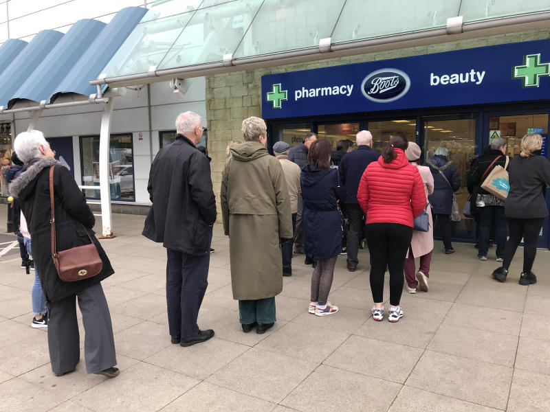 People queue outside a Boots pharmacy store in west London where stocks of hand sanitiser are limited to two per person. (Photo by Martin Keene/PA Images via Getty Images)