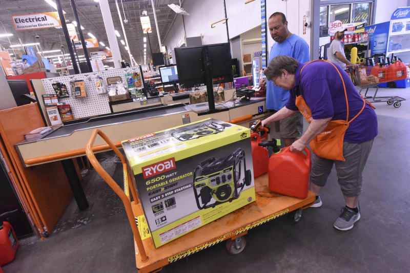 FILE - In this Sept. 2, 2019, file photo Delma Hewitt checks out Al Lombardi as he purchases a new generator and other supplies at the Home Depot in Monkey Junction, N.C. Backup power options range from gasoline-powered portable generators, which can cost $1,000 or more, to solar panels plus batteries, which cost tens of thousands of dollars to purchase and install. (Ken Blevins/The Star-News via AP, File)