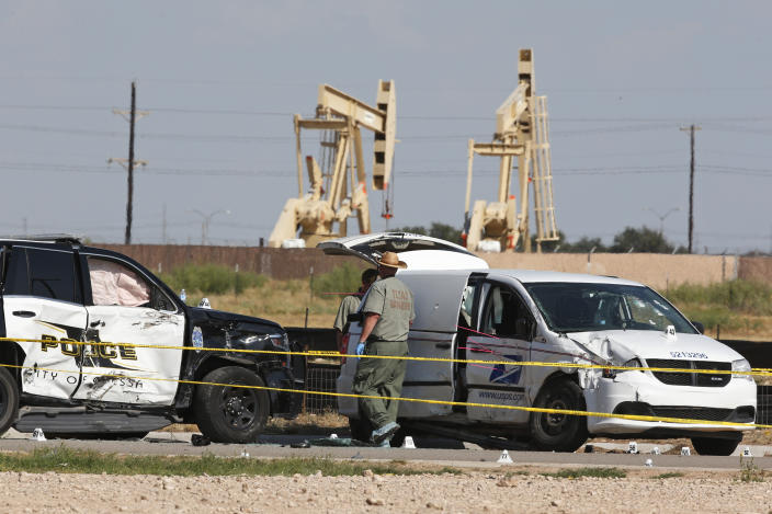 Law enforcement officials process the crime scene Sept. 1, 2019, in Odessa, Texas, from Saturday's shooting which ended with the alleged shooter being shot dead by police in a stolen mail van, right. (AP Photo/Sue Ogrocki)