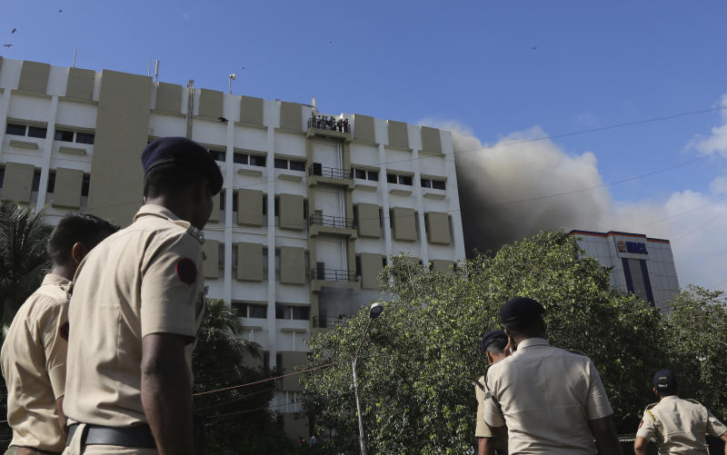 Police men look on as people awaiting rescue stand on the balcony of a nine-story building with offices of a state-run telephone company during a fire in Mumbai, India, Monday, July 22, 2019. (AP Photo/Rafiq Maqbool)