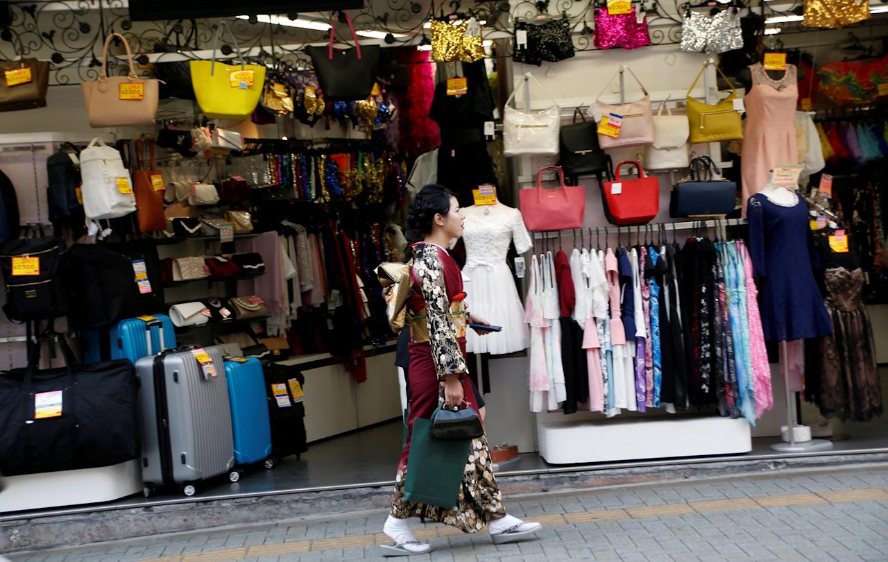 FILE PHOTO: A woman in a kimono walks past a shop in a shopping district in Tokyo, Japan March 23, 2017.   REUTERS/Kim Kyung-Hoon/File Photo                    GLOBAL BUSINESS WEEK AHEAD - SEARCH GLOBAL BUSINESS 27 MAR FOR ALL IMAGES