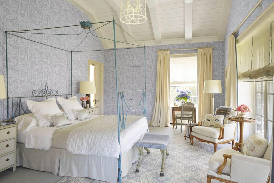 """<p>In this Long Island bedroom, designer <a href=""""http://frankdebiasi.com/"""" rel=""""nofollow noopener"""" target=""""_blank"""" data-ylk=""""slk:Frank de Biasi"""" class=""""link rapid-noclick-resp"""">Frank de Biasi</a> combines cosmopolitan comforts with antique Italian furnishings. At the foot of the painted iron bed lies a vintage bench in a Holland & Sherry wool. The custom <a href=""""https://fave.co/2L6b1ke"""" rel=""""nofollow noopener"""" target=""""_blank"""" data-ylk=""""slk:Le Manach"""" class=""""link rapid-noclick-resp"""">Le Manach</a> wallcovering creates a comforting atmosphere within the space.</p>"""