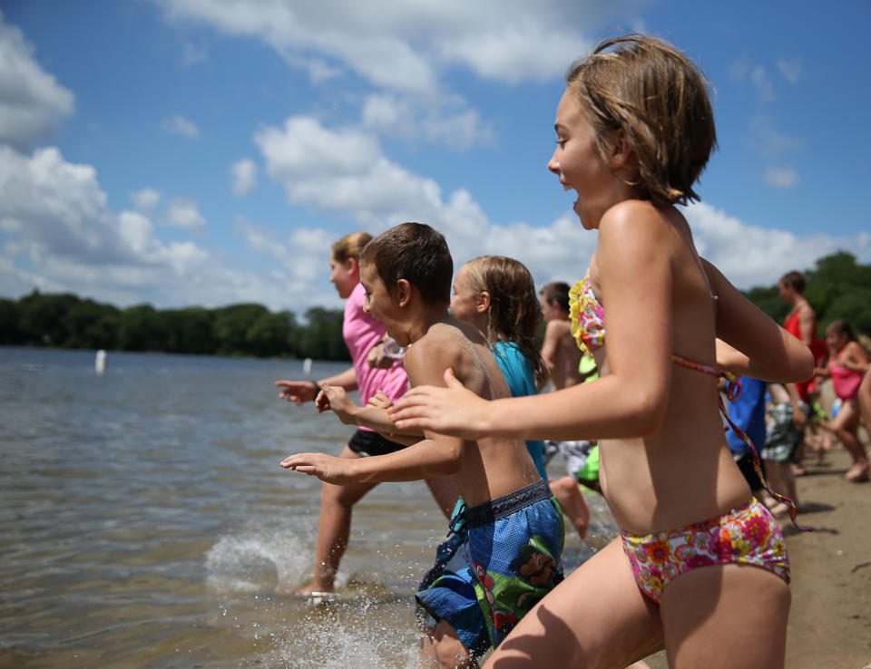 MILTON, MA - AUGUST 2: Houghton's Pond was the perfect place to cool off for kids from Old Colony YMCA  Summer Camp program. Madison Roach, 10, heads into the water with fellow camp goers. (Photo by Jonathan Wiggs/The Boston Globe via Getty Images)