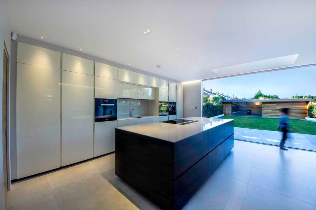 <p>The heart of the home (aka the kitchen) opens up stunningly onto the aforementioned garden, allowing indoor- and outdoor space to combine quite beautifully.</p><p>Notice how the kitchen's ultra modern style and clean-cut look contrasts from the garden's fresh greens and lush ambience.</p>  Credits: homify / New Images Ltd