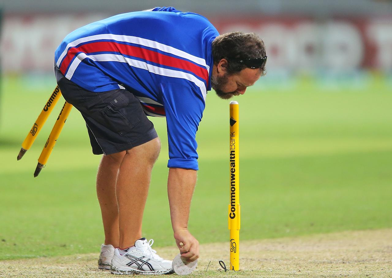 SYDNEY, AUSTRALIA - JANUARY 20:  A groundsman removes stumps after play was abandoned due to rain following game four of the Commonwealth Bank one day international series between Australia and Sri Lanka at Sydney Cricket Ground on January 20, 2013 in Sydney, Australia.  (Photo by Brendon Thorne/Getty Images)
