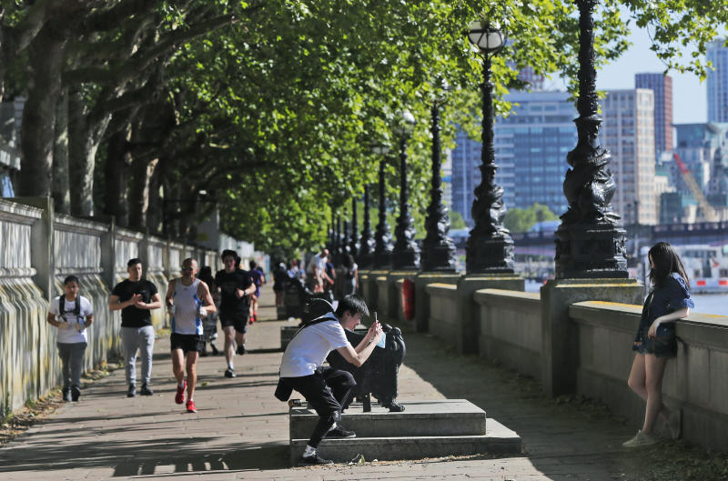 People enjoy the sunny and warm weather on the banks of the river Thames in London, Thursday, May 28, 2020 following the gradual easing of the COVID-19 lockdown, allowing more outdoor recreation and letting some shops and businesses reopen. (AP Photo/Frank Augstein)