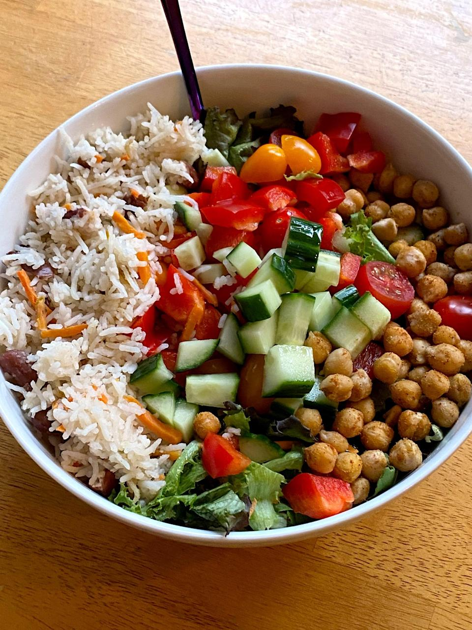 """<p>I paired a huge bowl of salad with chickpeas sautéed with garlic powder and cumin, and rice cooked with shredded carrots and kidney beans. Instead of an oil-based dressing, I drizzled it with my favorite flavored vinegar, <a href=""""https://www.amazon.com/Saratoga-Olive-Oil-Company-Cranberry/dp/B07175QJX5/ref=sr_1_1_sspa?dchild=1&amp;keywords=saratoga+oil+pear+cranberry+vinegar&amp;qid=1620328852&amp;sr=8-1-spons&amp;psc=1&amp;spLa=ZW5jcnlwdGVkUXVhbGlmaWVyPUExVzVLOVhSWUVTUkRRJmVuY3J5cHRlZElkPUEwMzE2MDQyM01STFZBVUMyM082VSZlbmNyeXB0ZWRBZElkPUEwMDE3NDgyMjlXSlJTS0ZGTU01VyZ3aWRnZXROYW1lPXNwX2F0ZiZhY3Rpb249Y2xpY2tSZWRpcmVjdCZkb05vdExvZ0NsaWNrPXRydWU="""" class=""""link rapid-noclick-resp"""" rel=""""nofollow noopener"""" target=""""_blank"""" data-ylk=""""slk:Cranberry Pear White Balsamic"""">Cranberry Pear White Balsamic</a> from Saratoga Olive Oil. </p>"""