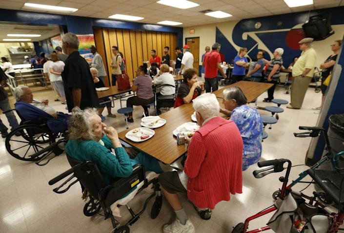 People at a Red Cross shelter set up at North Miami Beach Senior High School eat lunch, Friday, Sept. 8, 2017 before Irma made landfall in Florida.