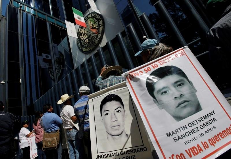 FILE PHOTO: Relatives hold poster with images of some of the 43 missing students of Ayotzinapa College Raul Isidro Burgos as they take part in a protest, in Mexico City