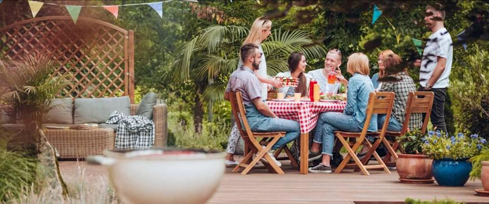 Group of people sitting in a backyard on a patio at a table, discussing.