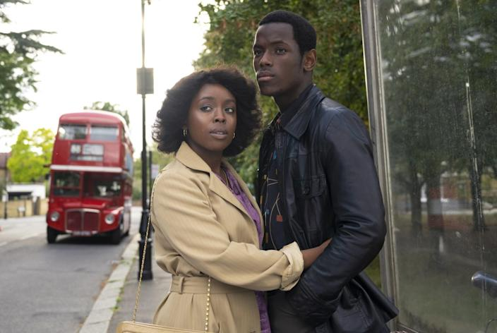 A couple embracing on the sidewalk with a red London bus behind them