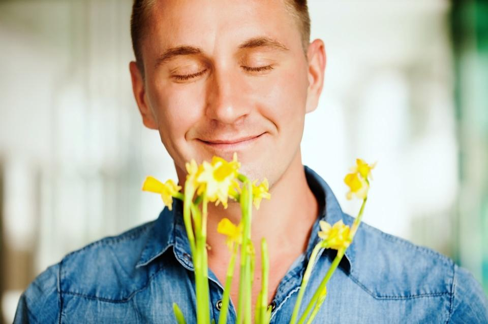 man smelling flowers