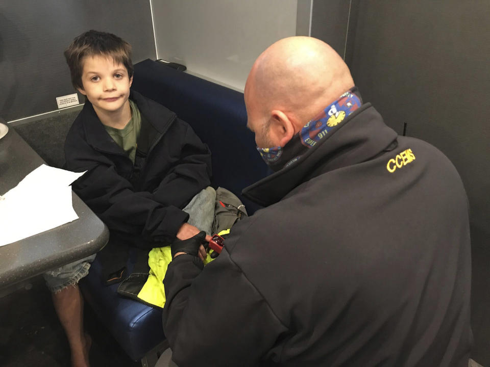 Image: 9-year-old Jordan Gorman is checked out by a Tennessee Bureau of Investigation employee after he was found in the woods near his home (Tennessee Bureau of Investigation / AP)