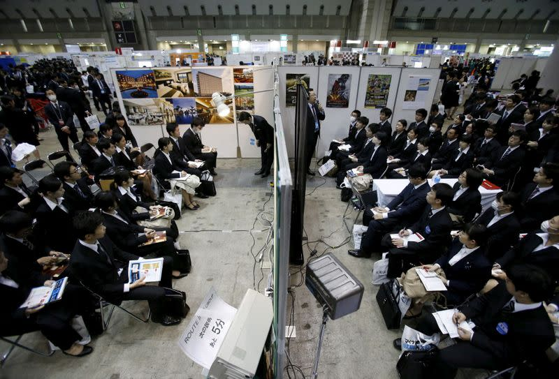 FILE PHOTO: Job seekers attend orientation sessions at company booths during a job fair held for fresh graduates in Tokyo