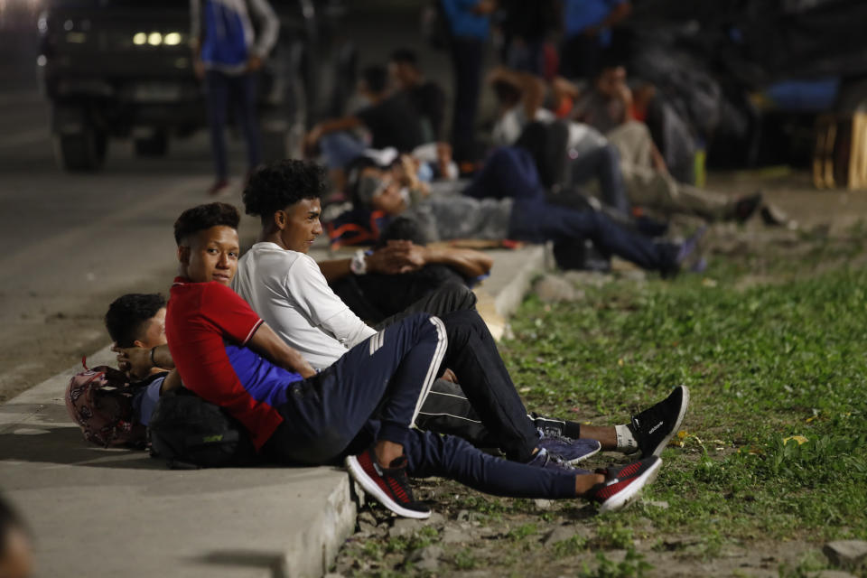 Migrants hoping to reach the distant U.S. border rest on the side of a highway, one kilometer from a police blockade, on the outskirts of San Pedro Sula, Honduras, Wednesday, Jan. 13, 2021. About 200 migrants began walking toward the border with Guatemala, two days before a migrant caravan was scheduled to depart the city. (AP Photo/Moises Castillo)