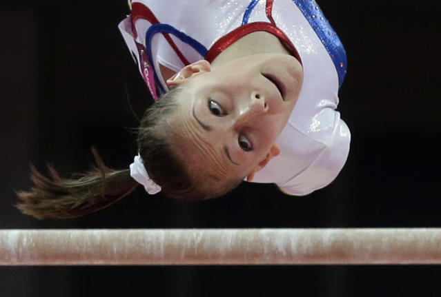 Romania's gymnast Diana Maria Chelaru eyes the bar during her performance on the uneven bars at Artistic Gymnastics women's team final at the 2012 Summer Olympics, Tuesday, July 31, 2012, in London. (AP Photo/Julie Jacobson)