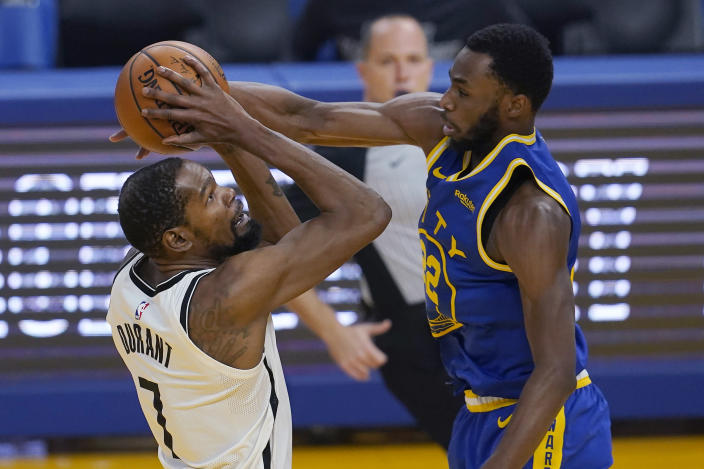 Brooklyn Nets forward Kevin Durant, left, shoots against Golden State Warriors forward Andrew Wiggins during the first half of an NBA basketball game in San Francisco, Saturday, Feb. 13, 2021. (AP Photo/Jeff Chiu)