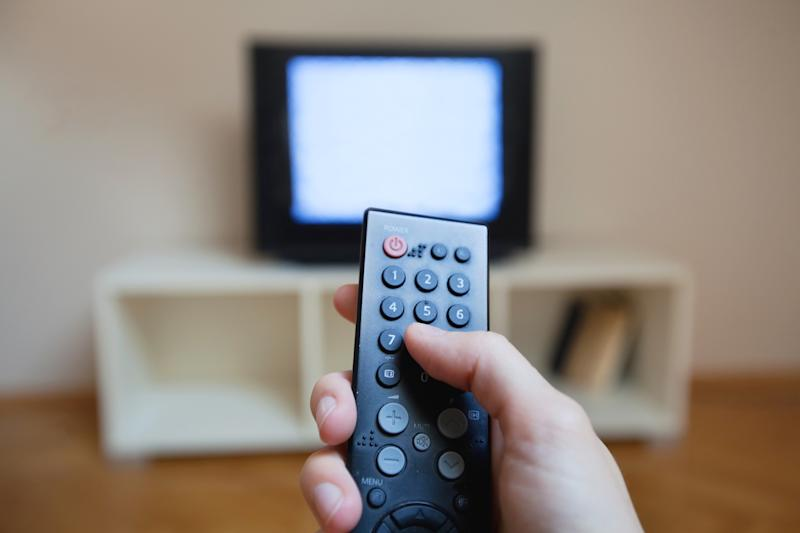 A hand holding a television remote and a TV showing static