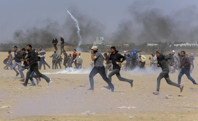 <p>Palestinian protesters run for cover from teargas fired by Israeli troops near the border fence, east of Khan Younis, in the Gaza Strip, Tuesday, May 15, 2018. Israel faced a growing backlash Tuesday and new charges of using excessive force, a day after Israeli troops firing from across a border fence killed 59 Palestinians and wounded more than 2,700 at a mass protest in Gaza. (Photo: Adel Hana/AP) </p>