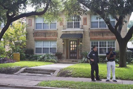 A Dallas police officer and a Dallas Fire Department Community officer, Shawn Williams (R) stand in front of the residence of a health worker at the Texas Health Presbyterian Hospital who has contracted Ebola in Dallas, Texas, October 12, 2014. REUTERS/Jaime R. Carrero