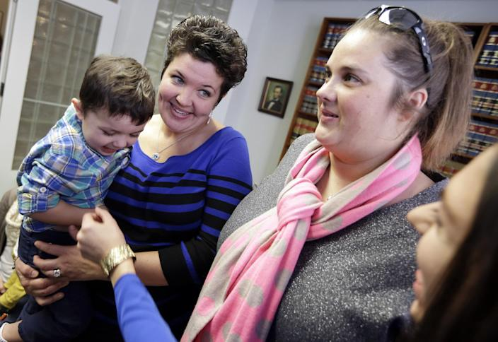 Nicole Yorksmith, left, holds her son while standing with her partner Pam Yorksmith, Monday, Feb. 10, 2014, following a news conference in Cincinnati. Four legally married gay couples filed a federal civil rights lawsuit Monday seeking a court order to force Ohio to recognize same-sex marriages on birth certificates despite a statewide ban. (AP Photo/Al Behrman)