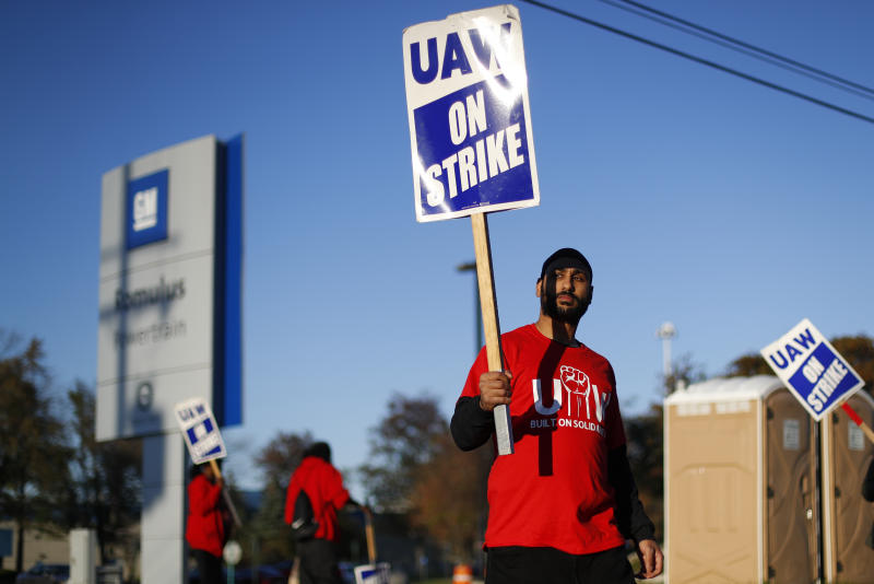 FILE - In this Oct. 9, 2019, file photo a member of the United Auto Workers walks the picket line at the General Motors Romulus Powertrain plant in Romulus, Mich. General Motors CEO Mary Barra joined negotiators at the bargaining table Tuesday, Oct. 15, an indication that a deal may be near to end a monthlong strike by members of the United Auto Workers union that has paralyzed the company's factories. (AP Photo/Paul Sancya, File)