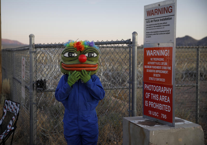 "Martin Custodio wears a Pepe mask while standing near razor wire at an entrance to the Nevada Test and Training Range near Area 51, Sept. 20, 2019, near Rachel, Nev. People came to visit the gate inspired by the ""Storm Area 51"" internet hoax. (Photo: John Locher/AP)"