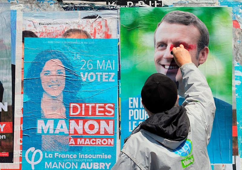 A supporter of French candidate for La France Insoumise party Marion Aubry, scribbles on a campaign poster of French president Emmanuel Macron in Saint-Jean-de-Luz, southwestern France, Tuesday, May 21, 2019, Voters in each 28 EU nations will choose lawmakers to represent them at the European Parliament for the next five years. (Photo: Bob Edme/AP)